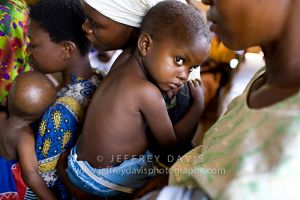 A CHILD CLUTCHES HIS MOTHER BEFORE MEDICAL REVIEW, RURAL HEALTH CLINIC, MALAWI, AFRICA