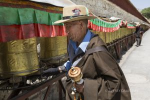 PILGRIM AT POTALA PALACE, PRAYER WHEELS, LHASA, TIBET