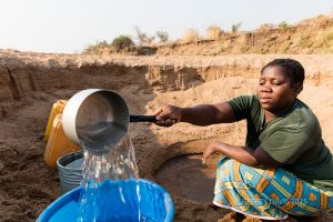 GATHERING FILTERED WATER FROM A RIVER BANK, ELIZABETH, 31 YEARS OLD, MALAMA VILLAGE, MFUWE, ZAMBIA